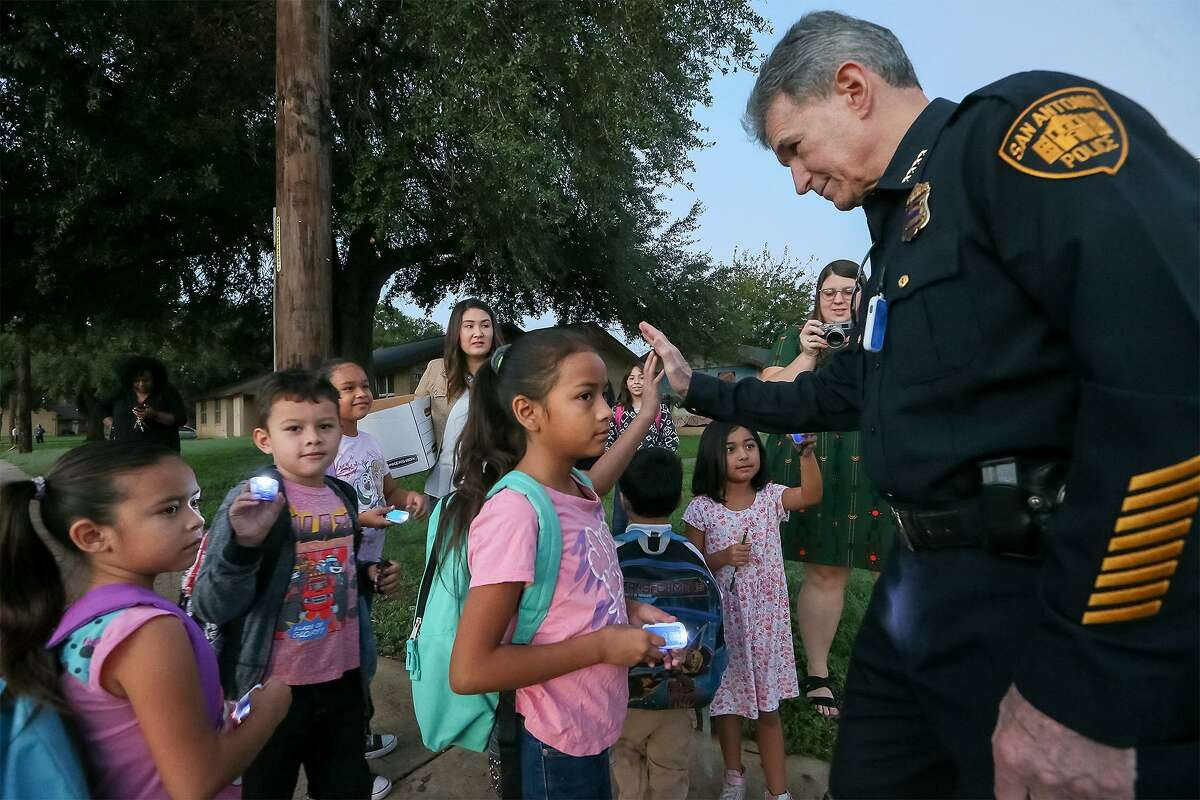 """San Antonio Police Chief William McManus high-fives children waiting to go to school in a """"Walking School Bus"""" organized by Safe Kids San Antonio on Wednesday, Oct. 10, 2018. Partners and volunteers joined the Walking School Bus at Cassiano homes and greeted students arriving at Sarah King Elementary."""