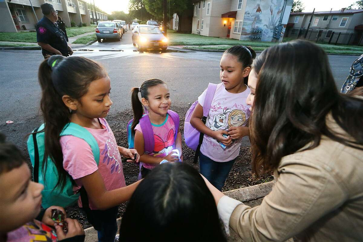 """Lily Lowder (right) with the Alamo Area Metropolitan Planning Organization hands out flashers to children preparing to go to school in a """"Walking School Bus"""" organized by Safe Kids San Antonio on Wednesday, Oct. 10, 2018. Partners and volunteers joined the Walking School Bus at Cassiano homes and greeted students arriving at Sarah King Elementary."""