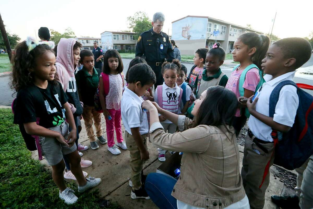 """Lily Lowder (below) with the Alamo Area Metropolitan Planning Organization pins flashers on children preparing to go to school in a """"Walking School Bus"""" organized by Safe Kids San Antonio as SAPD Chief William McManus talks to others on Wednesday, Oct. 10, 2018. Partners and volunteers joined the Walking School Bus at Cassiano homes and greeted students arriving at Sarah King Elementary."""