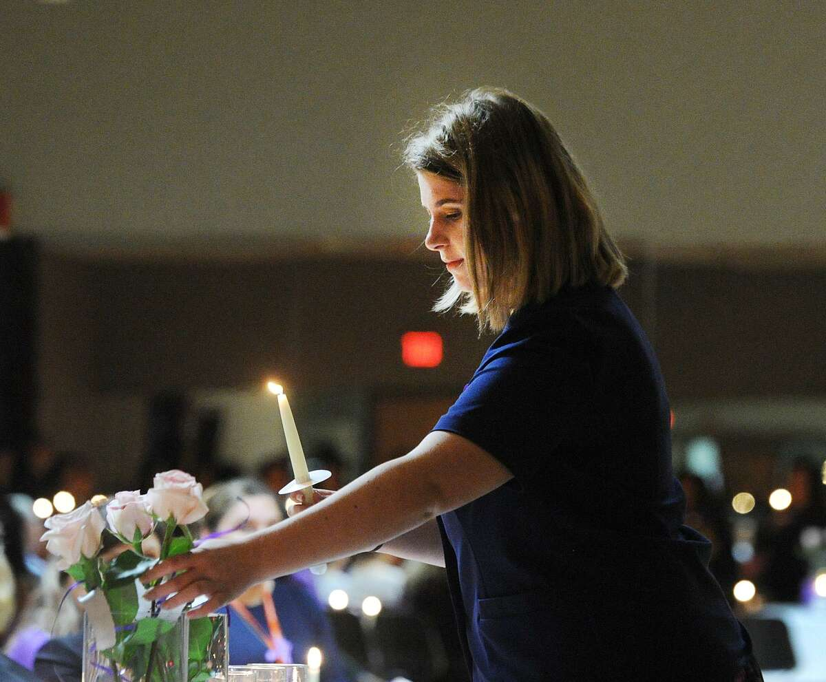 Holding a candle, Hannah Ross placed a white rose in a vase to honor a murdered victim of domestic violence and abuse during the YWCA of Greenwich Domestic Abuse Services annual Candlelight Vigil to honor the victims of domestic violence and abuse at the YWCA of Greenwich, Conn., Tuesday, Oct. 9, 2018. October is Domestic Violence Awareness Month.