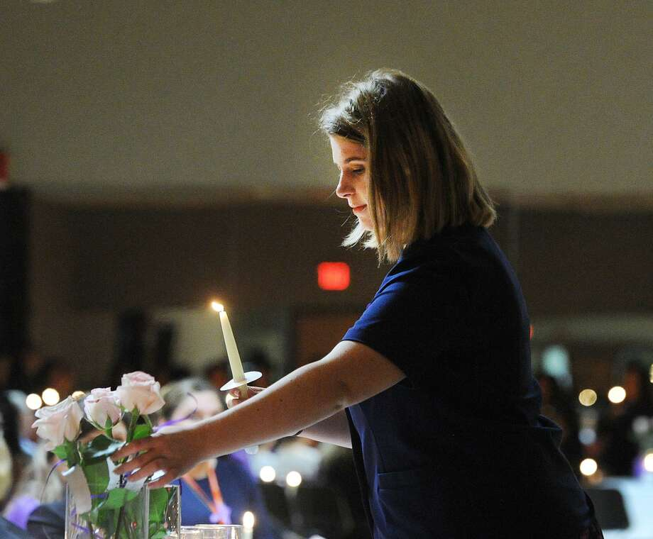 Holding a candle, Hannah Ross placed a white rose in a vase to honor a murdered victim of domestic violence and abuse during the YWCA of Greenwich Domestic Abuse Services annual Candlelight Vigil to honor the victims of domestic violence and abuse at the YWCA of Greenwich, Conn., Tuesday, Oct. 9, 2018. October is Domestic Violence Awareness Month. Photo: Bob Luckey Jr. / Hearst Connecticut Media / Greenwich Time