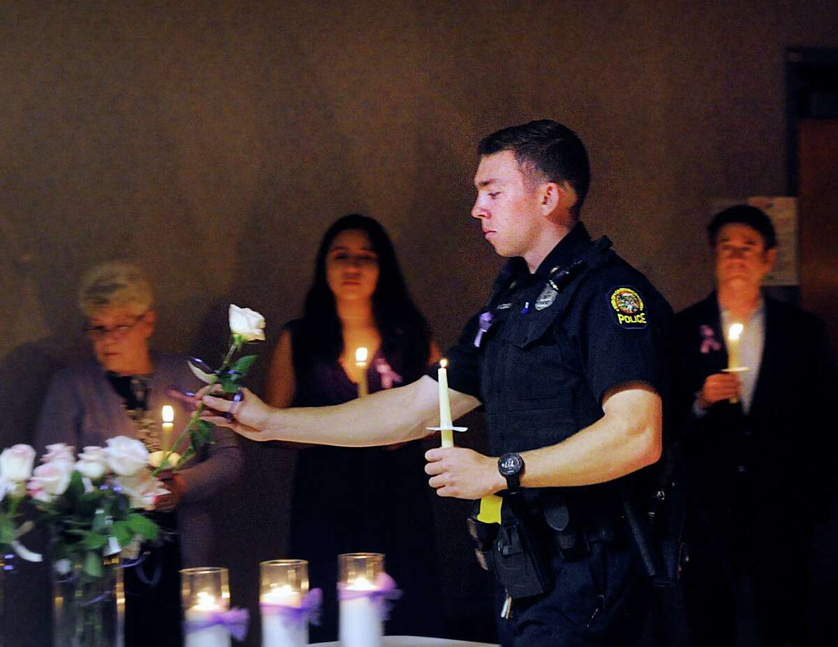 Greenwich Police Officer Ryan Daly placed a white rose in a vase to honor a murdered victim of domestic violence and abuse during the YWCA of Greenwich Domestic Abuse Services annual Candlelight Vigil to honor the victims of domestic violence and abuse at the YWCA of Greenwich, Conn., Tuesday, Oct. 9, 2018. October is Domestic Violence Awareness Month.
