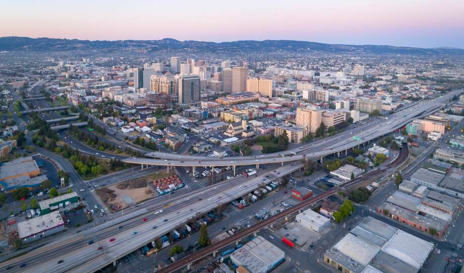 Aerial: Oakland City Skyline and freeway at sunset. California, USA Photo: Jonathan Clark/Getty Images