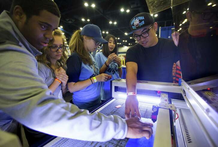 Anderson Ta, right, makes souvenir keychains with a laser cutter while promoting TXRX Labs during the 2017 Houston Maker Faire at George R. Brown Convention Center.