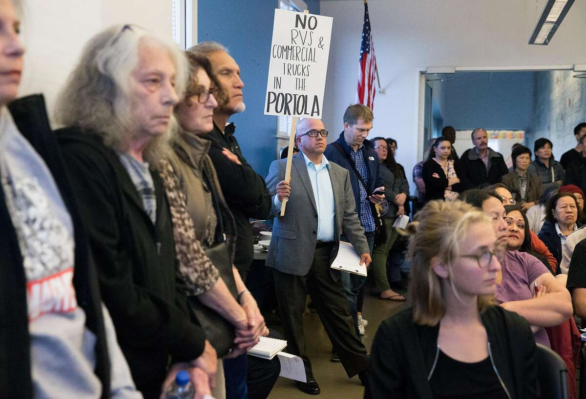 Petition organizer Richard Cairo, center, holds a homemade sign while joining neighbors of the Portola neighborhood at Palega Recreation Center to attend a community meeting surrounding RV and commercial vehicle parking issues in the Portola neighborhood of San Francisco, Calif. Tuesday, Oct. 9, 2018.