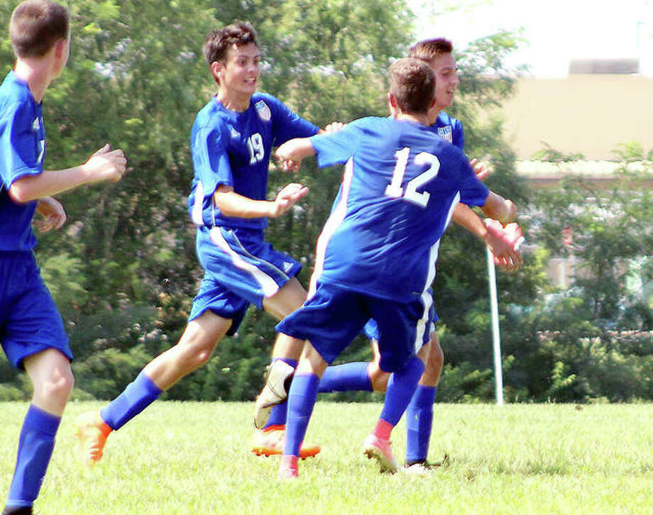 Carlinville's Landon Eades (12), Michael Douglas, left, and Matthew Schmidt (partially hidden) celebrate a goal earlier this season. The Cavies will face top-seeded Quincy Notre Dame at 5 p.m. Friday in the championship game of the Carlinville Class 1A Regional at Loveless Park. Photo: Pete Hayes | The Telegraph