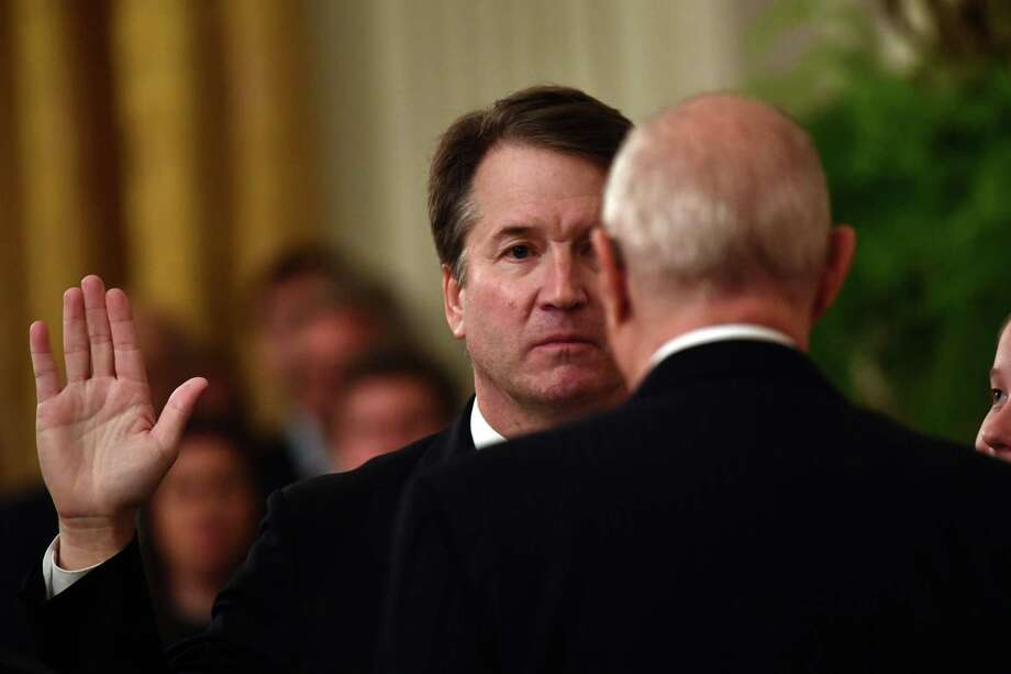 Brett Kavanaugh is sworn-in as Associate Justice of the U.S. Supreme Court by Associate Justice Anthony Kennedy on Monday at the White House. Photo: BRENDAN SMIALOWSKI /AFP /Getty Images / AFP or licensors