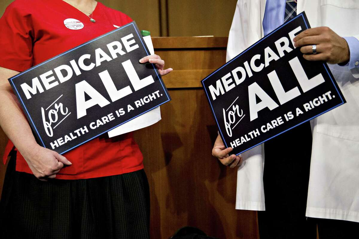 Attendees hold signs while waiting for a health care bill news conference to begin on Capitol Hill in Washington, D.C., U.S., on Wednesday, Sept. 13, 2017. Fifteen Senate Democrats are flirting with a single-payer health-care system that would expand Medicare coverage to all Americans, marking a shift within the party on what was once viewed as a politically treacherous issue that attracted little support from lawmakers. Photographer: Andrew Harrer/Bloomberg ORG XMIT: 775043578