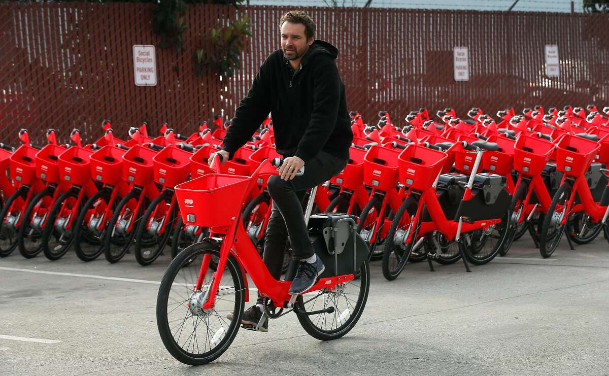 Jump Bike founder and CEO Ryan Rzepecki rides past some of the e-assist bicycles ready to hit the road in San Francisco, Calif. on Wednesday, Jan. 17, 2018. Jump is deploying 250 of the bike-share electric bicycles on the streets of the city Thursday and have plans to add another 250 to the fleet later in the year.