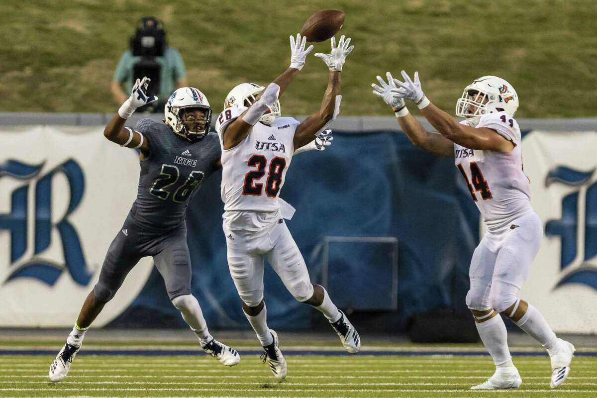 UTSA defensive back Cassius Grady (white) intercepts a pass intended for Rice receiver Aaron Cephus (grey) during the first half of a college football game at Rice Stadium on Saturday, Oct 6, 2018, in Houston.