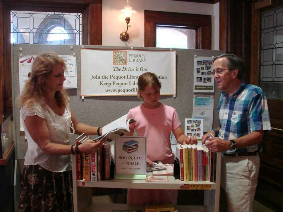 Getting ready for the 50th annual Pequot Library book sale are Susan Ei, children's librarian; volunteer Charlotte Meyer; and Dan Snydacker, executive director of the Pequot Library. Photo: Contributed Photo / Fairfield Citizen