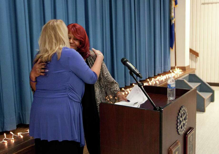 Deb Greenwood, left, of the Center for Family Justice, hugs Priscilla, a domestic violence survivor who spoke during the vigil at the Trumbull Library. Priscilla did not give her last name. Photo: Christian Abraham / Hearst Connecticut Media / Connecticut Post