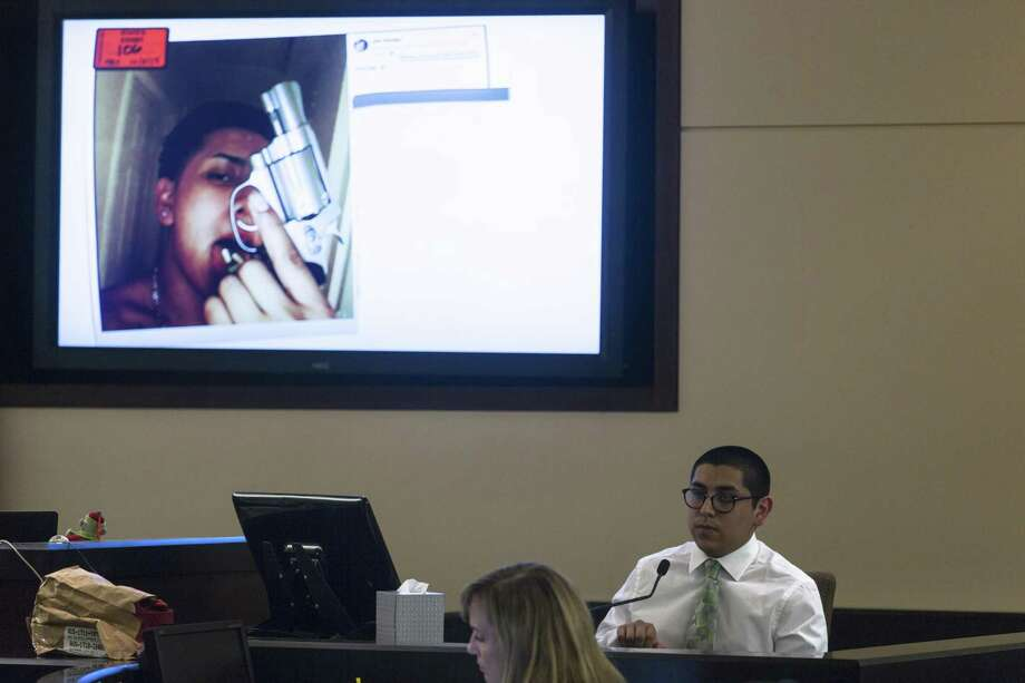 Jonathan Andrew Perales testifies in his own defense Wednesday in Judge Melisa Skinner's 290th Criminal District Court. On the screen, is a photo posted online of himself with Xanax pills on his tongue, displaying a gun like the one he used to kill homeowner Michael Clayton Robinson, 51, last year, after Perales was caught burglarizing the Robinson home in Universal City. On the stand, Perales admitted shooting Robinson but said Robinson shot first and he reacted instinctively by shooting back. He told the jury he knew Robinson had a right to shoot and that he, Perales, was just looking for something to steal, with no intention of hurting anyone,. Photo: William Luther /San Antonio Express-News / © 2018 San Antonio Express-News