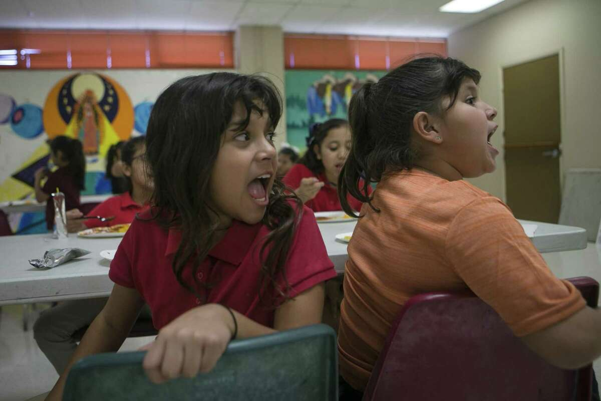 """Araceli Pena, left, and Kayleen Salinas, both 9, both yell """"Girl genuises!"""" as about 75 girls are called to attention by leaders Wednesday during the after-school program at West Side Girl Scout Leadership Center. The West Side Girl Scouts Leadership Center offers support to girls through programs to help them become future leaders."""
