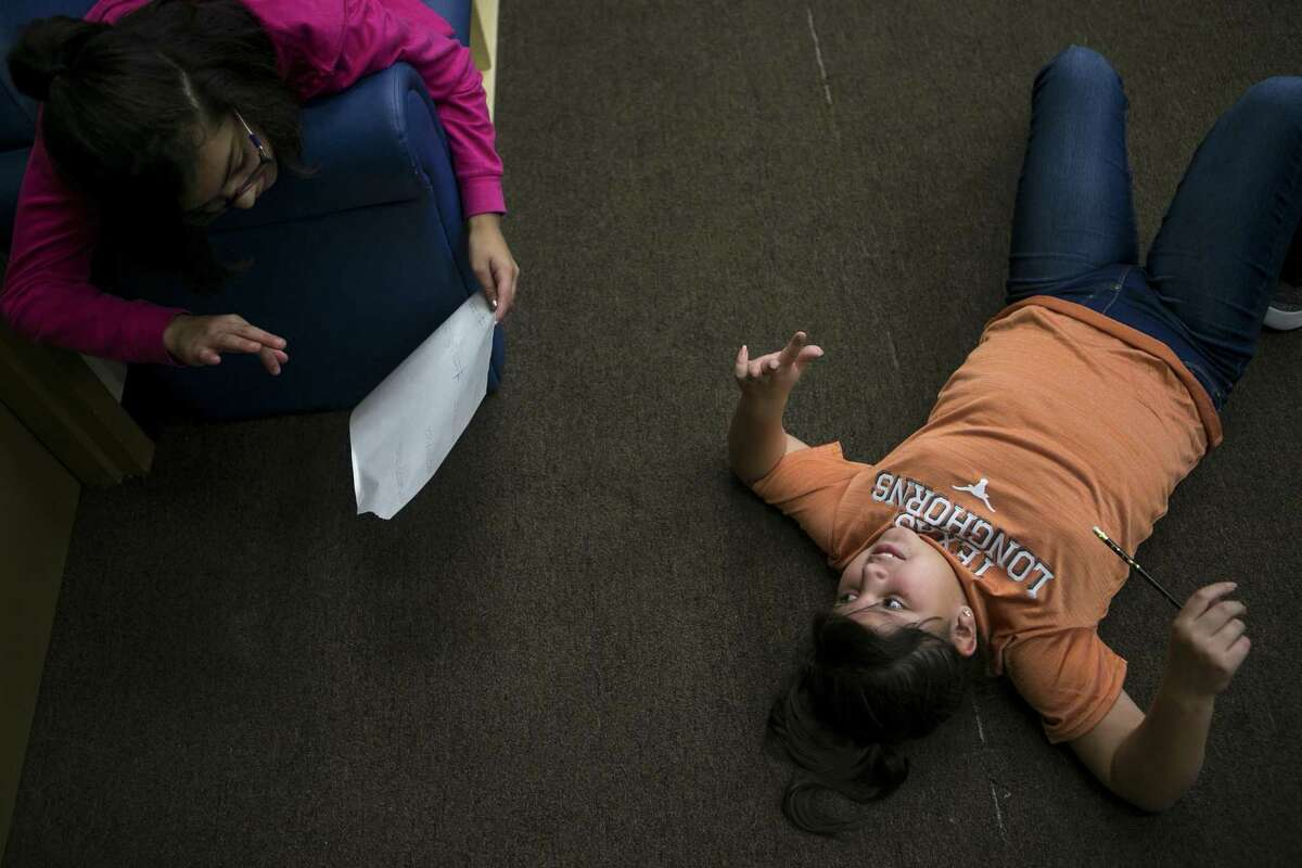 Miriam Ortiz, 10, helps Kayleen Salinas, 9, go though math facts as Kayleen lies on the floor Wednesday at the West Side Girl Scout Leadership Center.