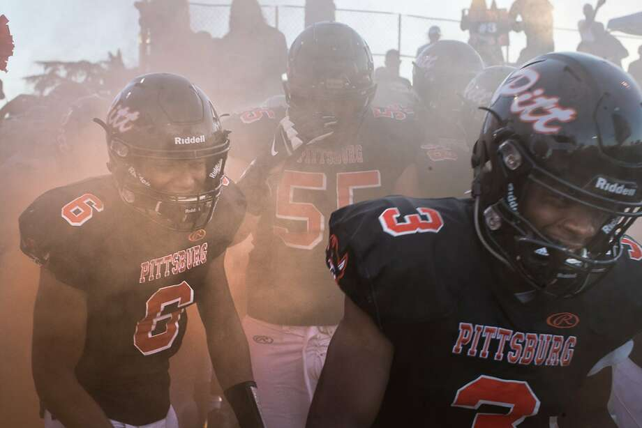 Pittsburg High School's QB Trey Turner (6) and Willie Harts III enter stadium through smoke at the start of the game against Serra High School on Friday, Sept. 7, 2018 in Pittsburg, CA. Photo: Paul Kuroda / Special To The Chronicle