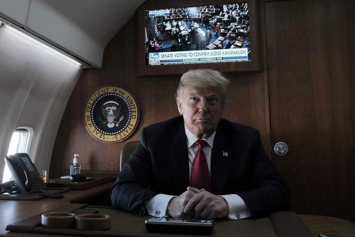 President Donald Trump speaks to reporters aboard Air Force One while a television shows the Senate as they vote on the confirmation of Judge Brett Kavanaugh to the Supreme Court, at Joint Base Andrews in Maryland, Oct. 6, 2018. Trump was headed to a campaign rally in Kansas on Saturday as a deeply divided Senate was poised to confirm Kavanaugh. (Pete Marovich/The New York Times)
