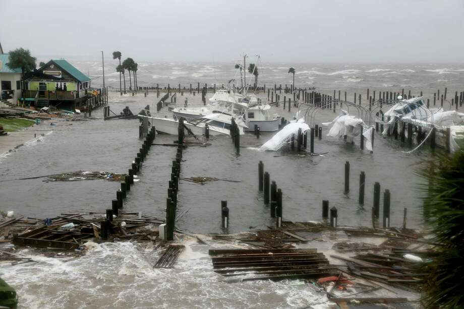 Storm Surge retreats from inland areas, foreground, where boats lay sunk and damaged at the Port St. Joe Marina, Wednesday, Oct. 10, 2018 in Port St. Joe, Fla. Supercharged by abnormally warm waters in the Gulf of Mexico, Hurricane Michael slammed into the Florida Panhandle with terrifying winds of 155 mph Wednesday, splintering homes and submerging neighborhoods. (Douglas R. Clifford/Tampa Bay Times via AP) Photo: Douglas R. Clifford / Tampa Bay Times
