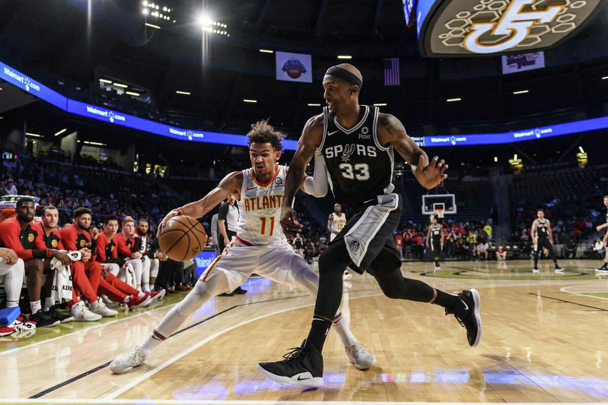 Spurs forward Dante Cunningham crowds rookie guard Trae Young, who later won the game for Atlanta with a long 3-pointer over Bryn Forbes in the closing seconds.