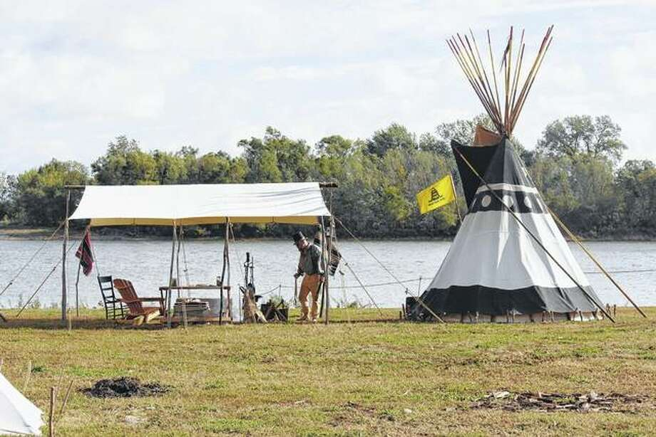 A man sets up camp on the banks of the Illinois River during Kampsville Old Settler Days. The event, which recalls the early days of Calhoun County, includes campers who spend the weekend living in teepees or canvas tents. Photo: Photo Provided