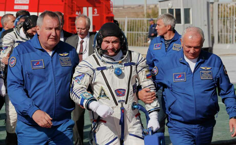 Director General of the Russia state corporation Roscosmos Dmitry Rogozin, right, accompanies Russian cosmonaut Alexey Ovchinin, crew members of the mission to the International Space Station, ISS, to the rocket prior the launch of Soyuz-FG rocket at the Russian leased Baikonur cosmodrome, Kazakhstan, Thursday, Oct. 11, 2018. (Yuri Kochetkov, Pool Photo via AP) Photo: Yuri Kochetkov, AP / Copyright 2018 The Associated Press. All rights reserved