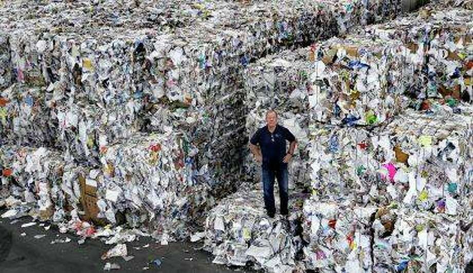 Ben Harvey, an owner at EL Harvey & Sons, a waste and recycling company, stands on bundles of residential mixed fiber. The company is stacking and holding onto about 2,500 tons of the material awaiting a destination where a recycler will process the bundles. Recycling programs across the United States are shutting down or scaling back because of a global market crisis blamed on contamination at the curbside bin. Photo: Charles Krupa   AP