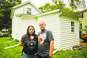 Ari Parsons, left, and Ryan Gerulski, right, pose for a portrait in the backyard of their home on the 1000 block of Elizabeth Street on Wednesday in Midland. The couple awoke around 4:30 a.m. on Friday when Ari's 9-year-old daughter told them there was a man in her bedroom. The man then exited through the second-story window, jumped to the ground and fled. (Katy Kildee/kkildee@mdn.net)