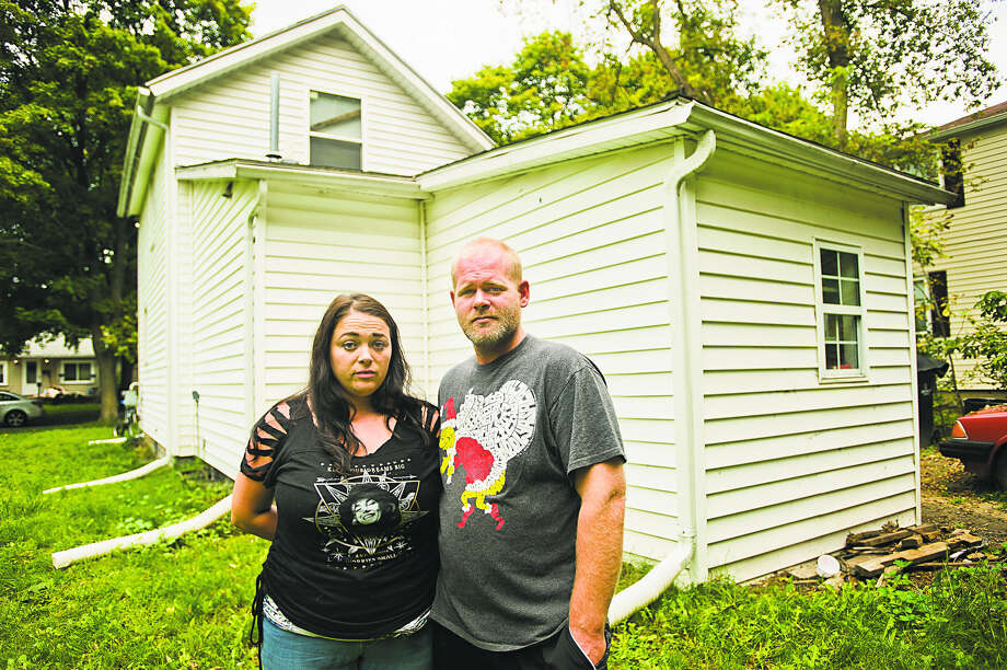 Ari Parsons, left, and Ryan Gerulski, right, pose for a portrait in the backyard of their home on the 1000 block of Elizabeth Street on Wednesday in Midland. The couple awoke around 4:30 a.m. on Friday when Ari's 9-year-old daughter told them there was a man in her bedroom. The man then exited through the second-story window, jumped to the ground and fled. (Katy Kildee/kkildee@mdn.net) Photo: Katy Kildee/kkildee@mdn.net