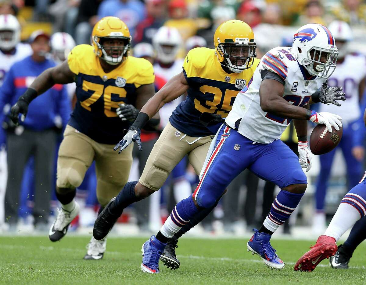GREEN BAY, WI - SEPTEMBER 30: LeSean McCoy #25 of the Buffalo Bills runs away from Jermaine Whitehead #35 of the Green Bay Packers and Mike Daniels #76 during the first quarter of a game at Lambeau Field on September 30, 2018 in Green Bay, Wisconsin.