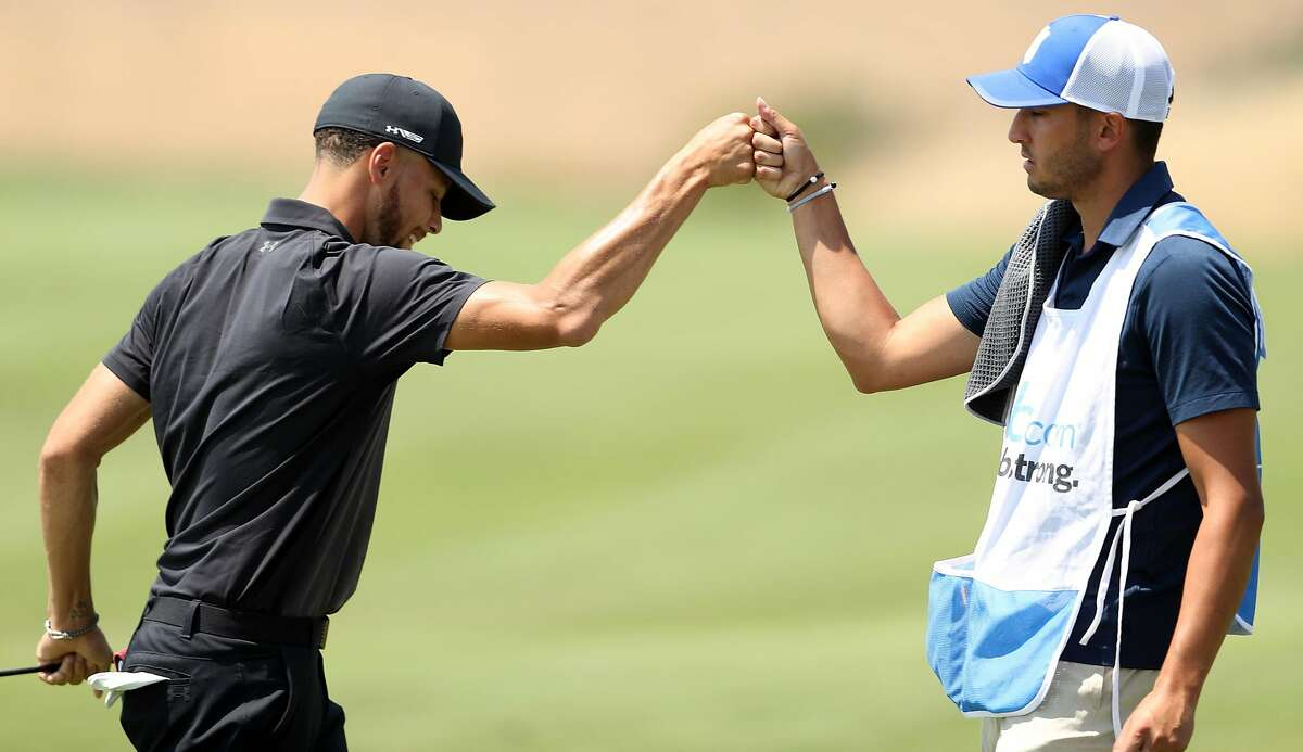 Golden State Warriors' Stephen Curry fist bumps his caddie, Jonnie west, after Curry made a birdie on 7th hole during 1st round of Ellie Mae Classic at TPC Stonebrae in Hayward, Calif. on Thursday, August 9, 2018.