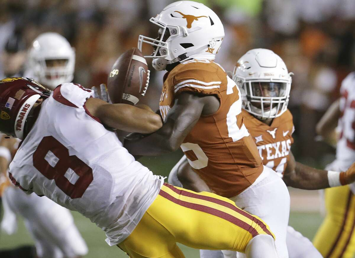 Longhorn defender B.J. Foster knocks the ball loose from Trojan receiver Amon-Ra St. Brown as UT plays USC at DKR Stadium on September 15, 2018.