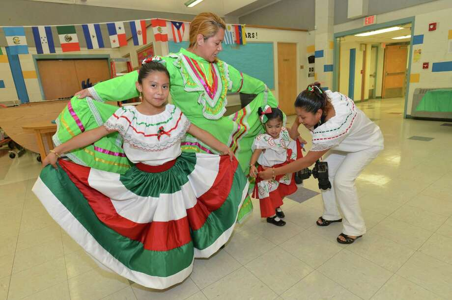 Guadalupe Marcelino and her nieces Emily and Leslie Marcelino get a hand fanning out their traditional Mexican dresses during the Fox Run School's Resource Center's Hispanic Heritage Celebration on Wednesday October 10, 2018 in Norwalk Conn. Photo: Alex Von Kleydorff / Hearst Connecticut Media / Norwalk Hour