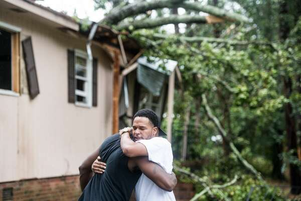 Hector Benthall, right, gets a hug from his neighbor Keito Jordan after remnants of Hurricane Michael sent a tree crashing into Benthall's home on October 11, 2018 in Columbia, South Carolina. Jordan was the first responder to the accident that sent at least one person to the hospital.