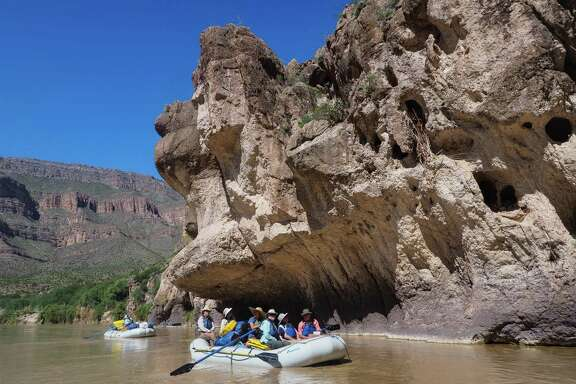 A raft glides under a knobby rock formation along the Rio Grande in Big Bend National Park.