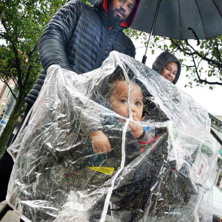 One-year-old Red Juarez stays dry while out for a rainy walk with parents Borey and Alice Juarez of Troy Thursday Oct. 11, 2018 in Troy, NY.  (John Carl D'Annibale/Times Union) Photo: John Carl D'Annibale, Albany Times Union / 20045101A