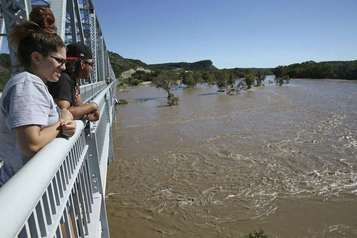 Natalie White and Anthony Rodriguez of Odessa stand on a bridge over the flooding, muddy South Llano River in Junction earlier this week. The spring-fed river, usually a narrow ribbon of clear blue/green water, saw its level jump almost 30 feet after as much as a foot of rain fell on the watershed in a few hours.
