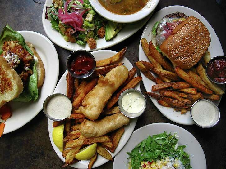 An array of food from The Esquire Tavern. Clockwise from left: shrimp sandwich, tortilla soup, bison burger with chile-salt fries, corn salad and fish and chips.