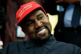 Rapper Kanye West smiles as he listens to a question from a reporter during a meeting in the Oval Office of the White House with President Donald Trump, Thursday, Oct. 11, 2018, in Washington.