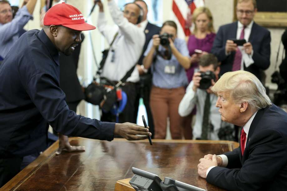 Rapper Kanye West , left, shows a picture of a plane on a phone to U.S. President Donald Trump during a meeting in the Oval office of the White House on October 11, 2018 in Washington, DC. Photo: Pool/Getty Images