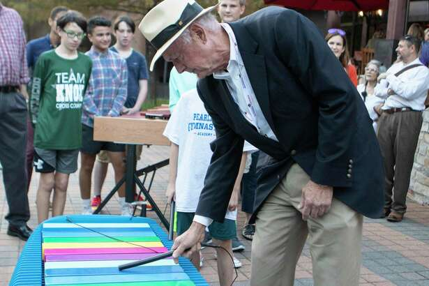 Why Sit When You Can Play underwriter Alex Sutton tests out the bench modeled after an xylophone during an unveiling Wednesday, Oct. 10, 2018 at Waterway Square in The Woodlands. The Woodlands Arts Council unveiled six benches as part of phase three of the art bench project.