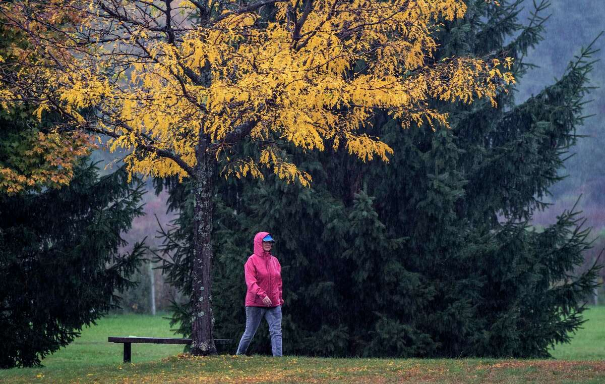 A person braves the inclement weather for a walk in The Crossings at Colonie Thursday Oct.11, 2018 in Colonie, N.Y. (Skip Dickstein/Times Union)