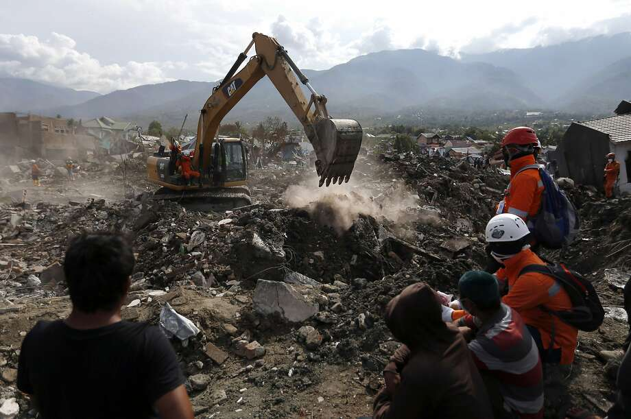 Rescue workers dig through rubble searching for earthquake /tsunami victims in Palu. The grim search is nearing its end almost two weeks after the double disasters hit the remote city. Photo: Dita Alangkara / Associated Press