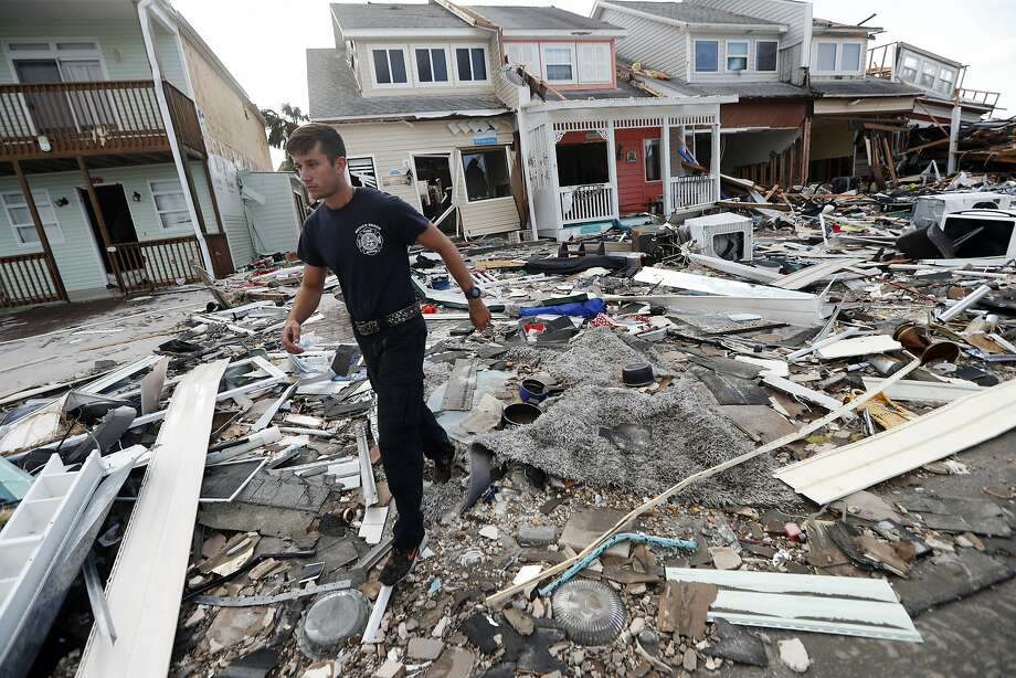 Firefighter Austin Schlarb performs a door to door search in the aftermath of Hurricane Michael in Mexico Beach, Fla. Photo: Gerald Herbert / Associated Press