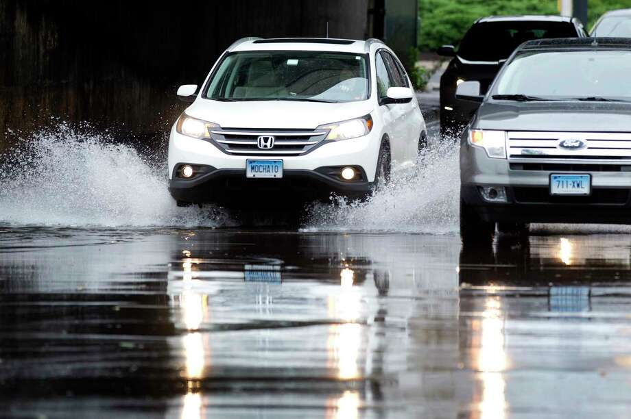 Cars drive through a growing puddle following a brief rain storm at the intersection of Canal St. and North State St. in Stamford, Conn. on Thursday, Oct. 11, 2018. Photo: Michael Cummo, Hearst Connecticut Media / Stamford Advocate
