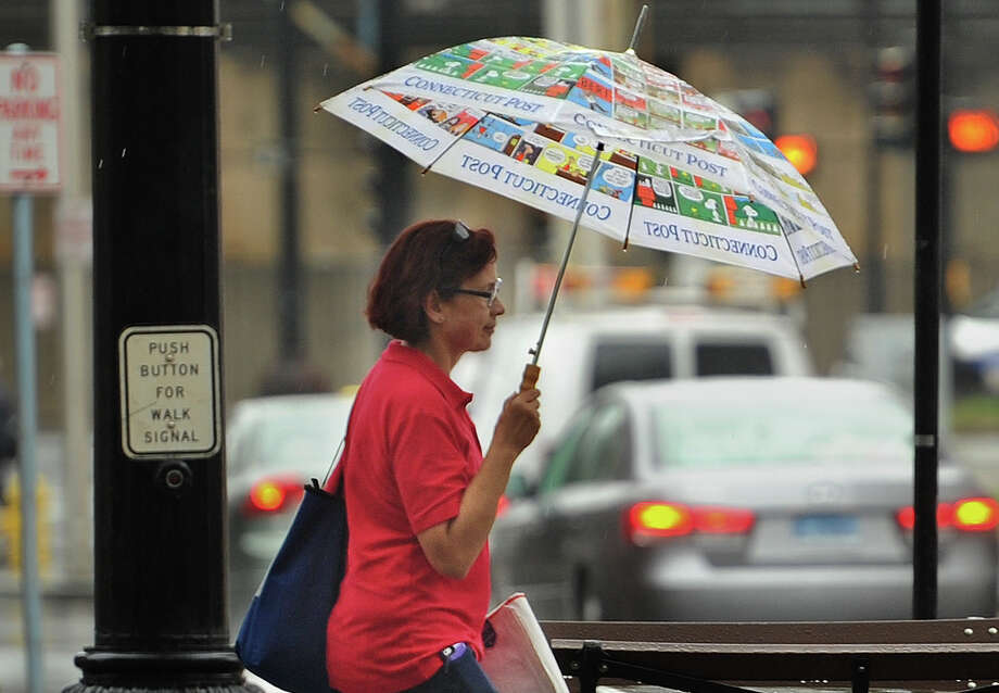 A woman stays dry beneath a colorful umbrella during heavy rains on Main Street in Bridgeport, Conn. on Thursday, October 11, 2018. Photo: Brian A. Pounds, Hearst Connecticut Media / Connecticut Post