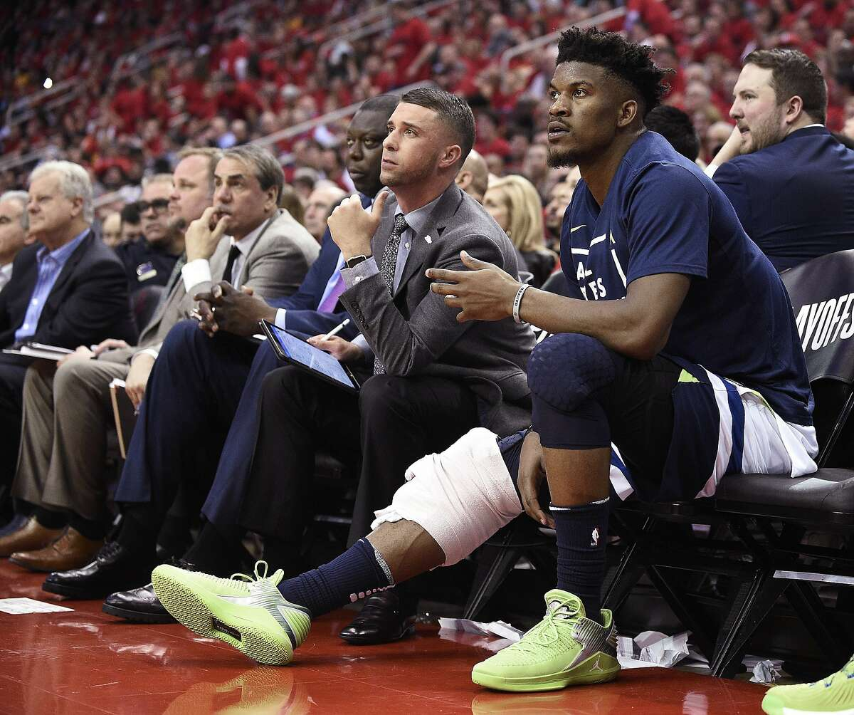 FILE - In this April 25, 2018, file photo, Minnesota Timberwolves guard Jimmy Butler, right, watches from the bench during the second half in Game 5 of the team's first-round NBA basketball playoff series against the Houston Rockets, in Houston. With Butler's status still unresolved, coach Tom Thibodeau and the Timberwolves head toward the season coming off the franchise's first playoff appearance in 14 years but carrying yet a still-cloudy outlook despite the super-max contract Karl-Anthony Towns.(AP Photo/Eric Christian Smith, File)