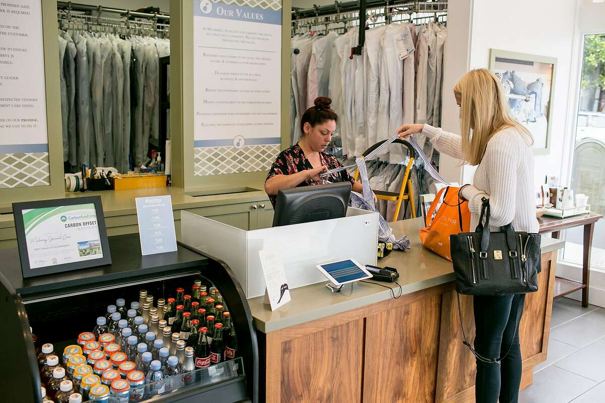 Nolina Luna, left, helps a customer at Mulberrys Garment Care in the Marina on Thursday, Oct. 11, 2018 in San Francisco, Calif. Mulberrys, a Minnesota dry cleaning company, is buying Laundry Locker making it the largest laundry company in Northern California.