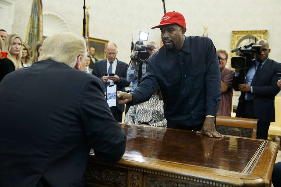 Rapper Kanye West shows President Donald Trump a photograph of a hydrogen plane during a meeting in the Oval Office of the White House, Thursday, Oct. 11, 2018, in Washington. (AP Photo/Evan Vucci) Photo: Evan Vucci, Associated Press