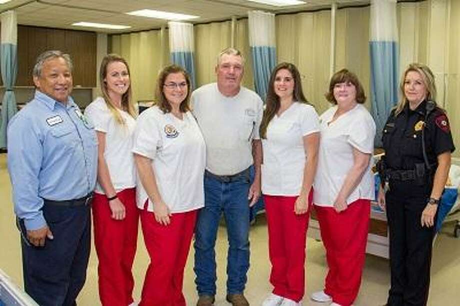 Electrician Gary Glover, center, stands surrounded by the people who helped revive him after he was electrocuted Sept. 19 on campus in Texas City. From left are COM electrician Lorrin Ching, student nurses Rachel Cunningham, Shanee Scribner, Alexis Boettcher and Andrea Strickland, and COM police Lt. Jill Hammond.