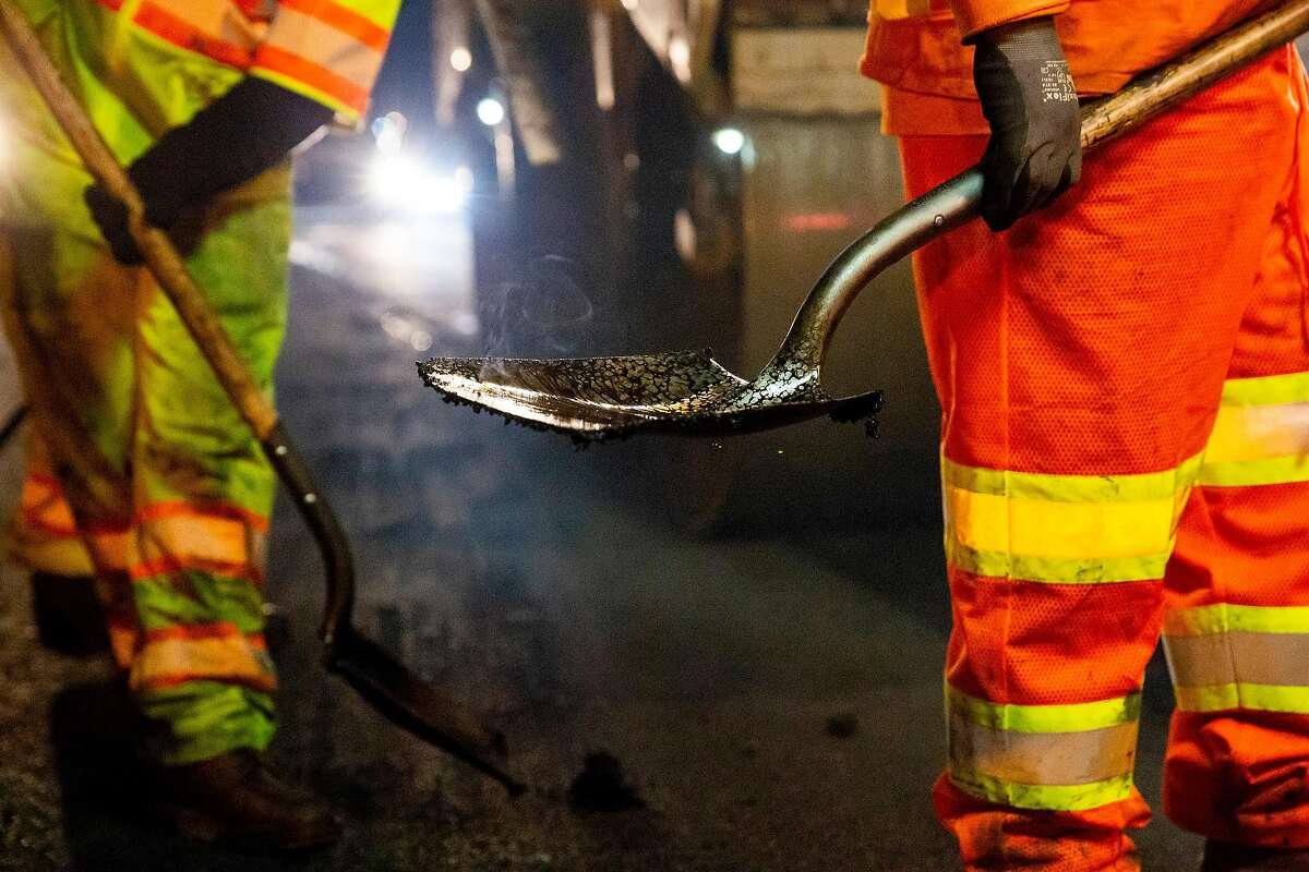 Steam rises from a shovel as O.C. Jones and Sons contractors working with CalTrans pave rubberized hot-mix asphalt on two of the Southbound lanes of the I-880 freeway in Hayward, Calif. on Wednesday, Oct. 9, 2018.